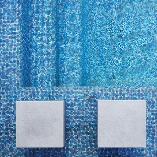 Ispirazione per una piscina a sfioro infinito design rettangolare di medie dimensioni e in cortile con pedane e una dépendance a bordo piscina