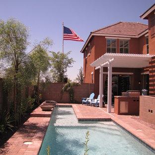 Foto de piscina de estilo americano, grande, rectangular, en patio trasero, con adoquines de ladrillo