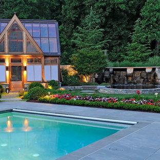 Diseño de piscina actual, grande, rectangular, en patio trasero, con adoquines de hormigón
