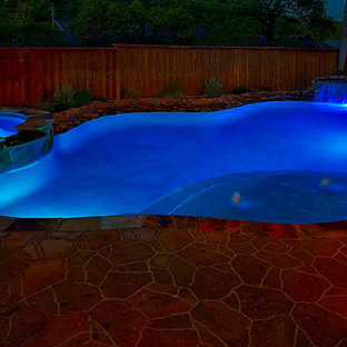 Design ideas for a large country backyard custom-shaped lap pool in Dallas with a water feature and concrete pavers.