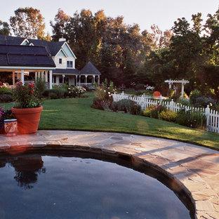 Exemple d'une grand piscine naturelle et arrière victorienne sur mesure avec des pavés en pierre naturelle.