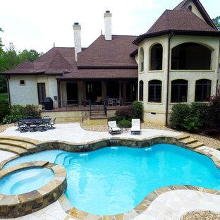 Idee per una grande piscina naturale vittoriana personalizzata dietro casa con una vasca idromassaggio e pedane