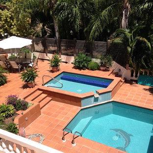 Modelo de piscina con fuente natural, tropical, de tamaño medio, a medida, en patio, con suelo de baldosas