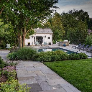 Modelo de piscina alargada, clásica renovada, grande, rectangular, en patio trasero, con adoquines de piedra natural
