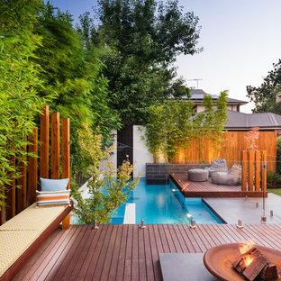 Diseño de piscina actual, rectangular, en patio trasero, con entablado