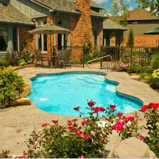 Ejemplo de piscina rural, de tamaño medio, a medida, en patio trasero, con suelo de hormigón estampado