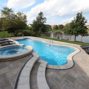 Imagen de piscinas y jacuzzis alargados, contemporáneos, grandes, a medida, en patio trasero, con adoquines de ladrillo