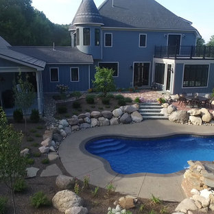 Inspiration for a mid-sized traditional backyard custom-shaped pool in New York with concrete slab.