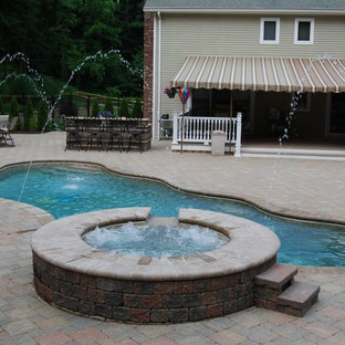Modelo de piscinas y jacuzzis clásicos, de tamaño medio, a medida, en patio trasero, con adoquines de ladrillo