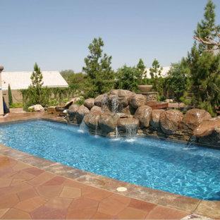 Foto de piscina con fuente de estilo americano, grande, rectangular, en patio trasero, con adoquines de piedra natural