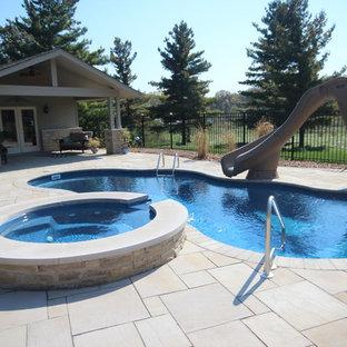 Inredning av en klassisk mellanstor anpassad pool på baksidan av huset, med marksten i tegel och vattenrutschkana