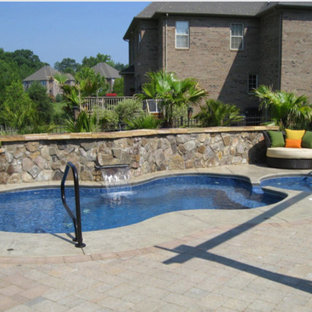 Design ideas for a mid-sized tropical backyard custom-shaped pool in Charlotte with a hot tub and brick pavers.