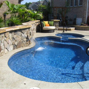 Inspiration for a mid-sized tropical backyard custom-shaped pool in Charlotte with a hot tub and brick pavers.