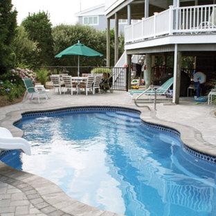 Imagen de piscina con tobogán costera, pequeña, a medida, en patio trasero, con adoquines de ladrillo