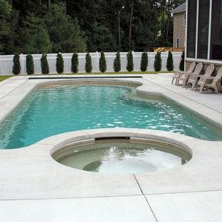 Imagen de piscina de estilo americano, de tamaño medio, a medida, en patio trasero, con adoquines de hormigón