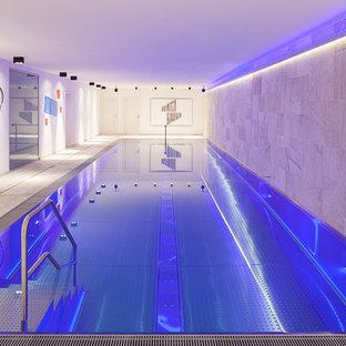 Foto de piscina actual, grande, rectangular y interior, con suelo de baldosas