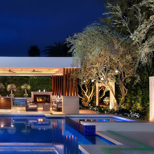 Inspiration for a contemporary backyard tile and custom-shaped infinity hot tub remodel in Orange County