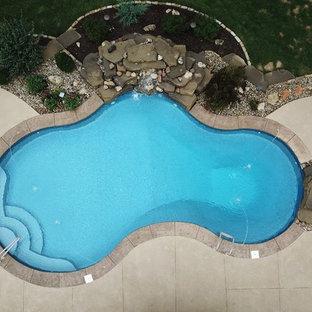 Modelo de piscina con fuente natural, clásica, de tamaño medio, a medida, en patio trasero, con suelo de hormigón estampado