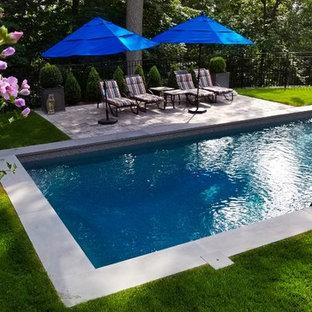 Foto de piscina alargada, tradicional, de tamaño medio, rectangular, en patio trasero, con adoquines de hormigón