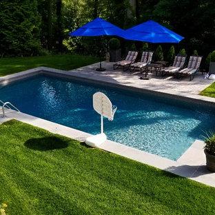 Modelo de piscina alargada, clásica, de tamaño medio, rectangular, en patio trasero, con adoquines de hormigón
