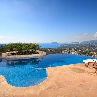 Modelo de casa de la piscina y piscina infinita, mediterránea, de tamaño medio, a medida, en patio, con suelo de baldosas