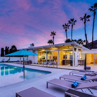 Immagine di una piscina monocorsia minimalista rettangolare dietro casa con lastre di cemento
