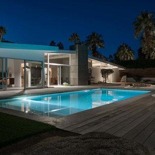 Imagen de piscinas y jacuzzis retro, de tamaño medio, rectangulares, en patio trasero, con losas de hormigón
