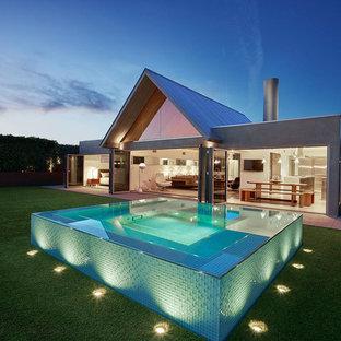 Diseño de piscina elevada, retro, de tamaño medio, rectangular, en patio trasero, con losas de hormigón