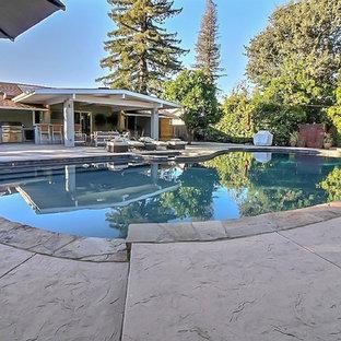 Esempio di una grande piscina classica rotonda dietro casa con una vasca idromassaggio e pavimentazioni in pietra naturale