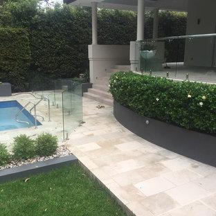 Modelo de piscina tradicional, en patio trasero, con suelo de baldosas