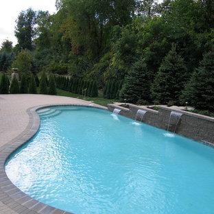 Diseño de piscina con fuente grande, tipo riñón, en patio trasero, con adoquines de ladrillo