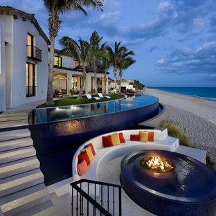 Esempio di una grande piscina a sfioro infinito tropicale personalizzata dietro casa con fontane e pavimentazioni in cemento