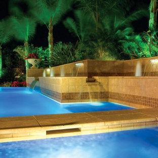 マイアミの大きい長方形トロピカルスタイルのおしゃれな裏庭プール (噴水、天然石敷き) の写真