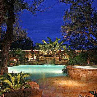 Esempio di una piscina naturale tropicale personalizzata di medie dimensioni e dietro casa con pavimentazioni in pietra naturale e una vasca idromassaggio