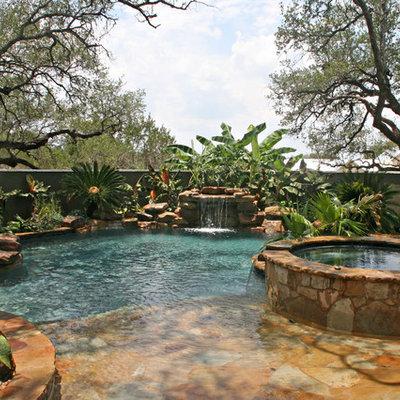 Hot tub - mid-sized tropical backyard stone and custom-shaped natural hot tub idea in Austin