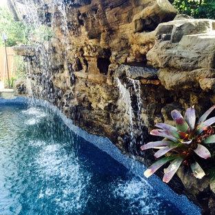 Imagen de piscina con tobogán natural, exótica, pequeña, a medida, en patio trasero, con losas de hormigón
