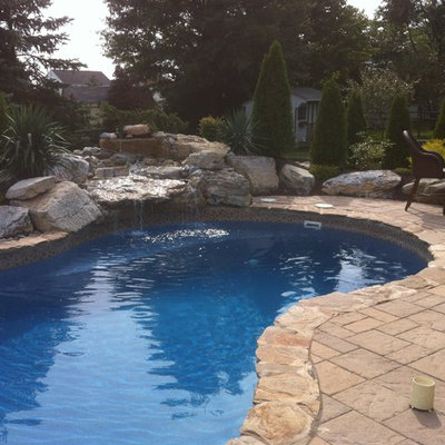 Example of a large mountain style backyard concrete paver and custom-shaped natural pool fountain design in Philadelphia