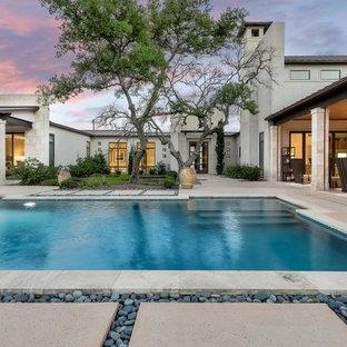 Ejemplo de piscina con fuente alargada, actual, rectangular, en patio trasero, con losas de hormigón