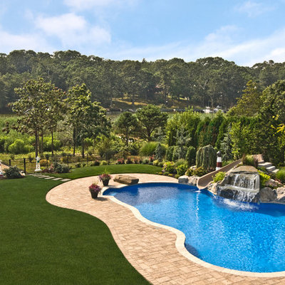 Example of a classic backyard custom-shaped pool design in New York