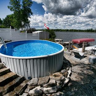 Diseño de piscina elevada, rústica, pequeña, redondeada, en patio delantero, con adoquines de piedra natural