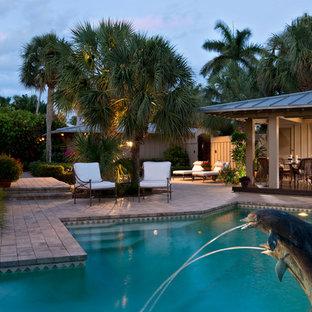 Ejemplo de piscina exótica, de tamaño medio, en patio lateral, con adoquines de piedra natural