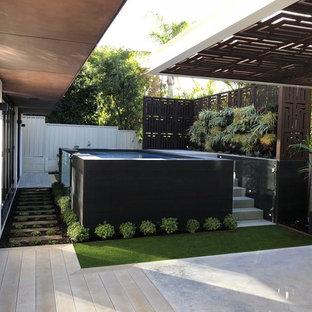 Foto de piscina elevada, industrial, de tamaño medio, rectangular, en patio trasero, con entablado