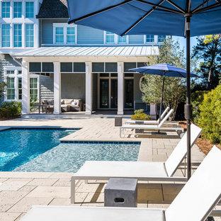 Immagine di un'ampia piscina stile marinaro personalizzata dietro casa con pavimentazioni in pietra naturale