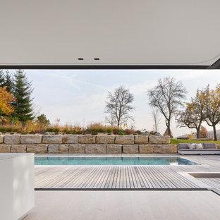 Immagine di una grande piscina monocorsia moderna rettangolare dietro casa con pedane