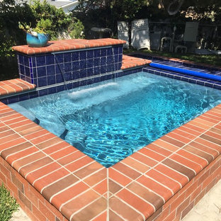 Design ideas for a small traditional backyard rectangular pool in Orange County with a water feature and brick pavers.