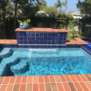 Photo of a small traditional backyard rectangular pool in Orange County with a water feature and brick pavers.