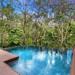 Photo of a mid-sized contemporary backyard rectangular infinity pool in Brisbane with decking.