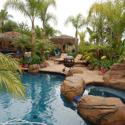Example of a mid-sized island style backyard concrete and custom-shaped natural hot tub design in Denver