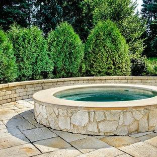 Foto di una piccola piscina fuori terra chic rotonda dietro casa con una vasca idromassaggio e pavimentazioni in pietra naturale