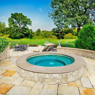 Imagen de piscinas y jacuzzis elevados, tradicionales, pequeños, redondeados, en patio trasero, con adoquines de piedra natural
